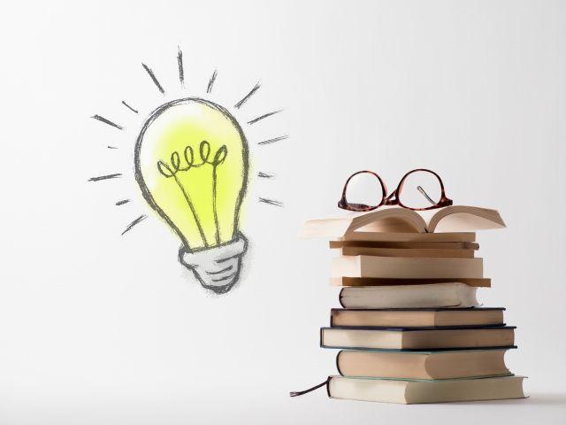 積まれた本と電球
